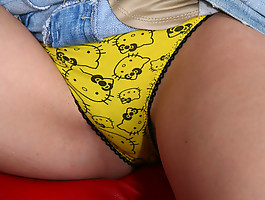 Young girl pulls her skirt up to show yellow panties
