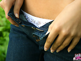 All natural beauty takes off her tight denim jeans in the woods